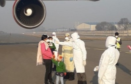 Indian passengers in China having their temperature taken before they board the Air India flight. PHOTO: ASIAN NEWS INTERNATIONAL