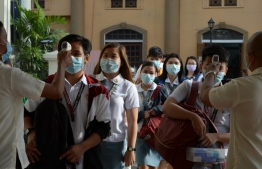 Students wearing protective face masks have their temperatures taken while entering their college campus in Manila on January 31, 2020. PHOTO: AFP