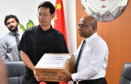 Foreign Minister Abdulla Shahid presents Maldives' donation of 1 million tuna cans to China, received by Chinese Ambassador Zhang Lizhong, on February 4, 2020. PHOTO: HUSSAIN WAHEED / MIHAARU