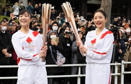 A torchbearer and actress Satomi Ishihara (R), one of the official ambassadors of the Tokyo 2020 torch relay, pose with the olympic torch during a rehearsal of the Tokyo 2020 Olympics torch relay in Tokyo on February 15, 2020. (Photo by STR / JIJI PRESS / AFP) /