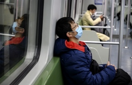 A subway passenger wearing a protective facemask sleeps on a train in Shanghai on February 14, 2020. - Youan Hospital is one of twenty hospitals in Beijing treating coronavirus patients. Six health workers have died from the COVID-19 coronavirus in China and more than 1,700 have been infected, health officials said on February 14, underscoring the risks doctors and nurses have taken due to shortages of protective gear. (Photo by NOEL CELIS / AFP)