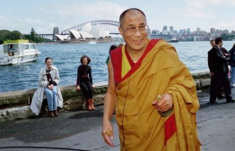 """Tibet's self-exiled spiritual leader (C), the 14th Dalai Lama, leaves Sydney harbour after conducting the last phase of the """"Kalachakra"""" or """"Wheel of time"""" ceremony on September 17, 1996. - The ceremony involved the pouring of a sand mandala into the harbour as a gesture for world peace. (Photo by David HANCOCK / AFP)"""