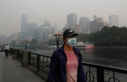 People wear breathing masks to protect themselves from a thick smoke haze from the bushfires, in Melbourne, Australia on Jan. 14, 2020. PHOTO: DAVID CROSLING