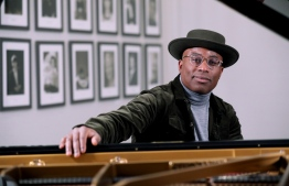 """British pianist and composer Alexis Ffrench poses for a photograph after giving an interview at Steinway & Sons in London on February 19, 2020. Composer and pianist Alexis Ffrench, one of Britain's few prominent black classical musicians, is on a mission """"to change the narrative"""" around the genre with his contemporary approach to the music. Isabel INFANTES / AFP"""
