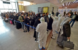 A medical team wearing protective outfit awaits to check Iraqi passengers returning from Iran upon their arrival at the Najaf International Airport on February 21, 2020, after Iran announced cases of coronavirus infections in the Islamic republic. (Photo by Haidar HAMDANI / AFP)