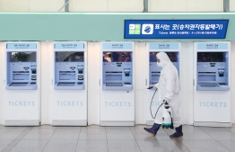 A railway worker wearing protective gear sprays disinfectant as part of preventive measures against the spread of the COVID-19 coronavirus, at a railway station in Seoul on February 25, 2020. (Photo by - / YONHAP / AFP)