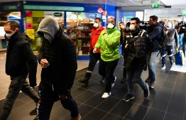 People wearing protective facemask are evacuated from the security zone where a bus comming from Milan is blocked at the train and bus station Lyon Perrache, due to suspected COVID-19 the novel coronavirus on board, in Lyon, on February 24, 2020. (Photo by JEAN-PHILIPPE KSIAZEK / AFP)