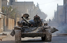Turkey-backed Syrian fighters ride a tank in the town of Saraqib in the eastern part of the Idlib province in northwestern Syria, on February 27, 2020. Syrian rebels reentered the key northwestern crossroads town of Saraqib lost to government forces earlier this month but fierce fighting raged on in its outskirts today, an AFP correspondent reported. Bakr ALKASEM / AFP