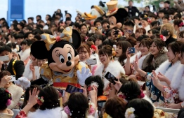 (FILES) This file photo taken on January 13, 2020 shows Disney character Minnie Mouse (L) greeting 20-year-old women and men during their 'Coming-of-Age Day' celebration at Tokyo Disneyland in Urayasu, in suburban Tokyo. - The operator of Tokyo's two Disney resorts, Disneyland and DisneySea, said on February 28, 2020 the parks would be closed for around two weeks on fears over the outbreak of the new coronavirus. (Photo by Kazuhiro NOGI / AFP)