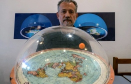 Brazilian self-avowed flat-Earth conspiracy theorist Anderson Neves holds a model of the flat earth surrounded by a dome during an interview with AFP in Sao Paulo, Brazil, on February 13, 2020. - Eleven million people in Brazil, 7% of its population, believe that the Earth is flat, according to Datafolha polling institute. (Photo by Florence GOISNARD / AFP)
