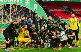 Manchester City's players celebrate with the trophy on the pitch after the English League Cup final football match between Aston Villa and Manchester City at Wembley stadium in London on March 1, 2020. Manchester City won the game 2-1. Glyn KIRK / AFP