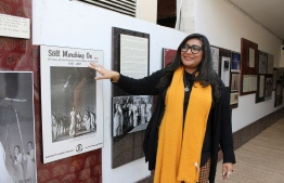 """In this picture taken on February 6, 2020, human rights award winner and founder of Pakistan's first cyber-harassment helpline, Nighat Dad, looks at a picture gallery at the ASR Resource Centre in Lahore. - With her flashing rings, green-streaked hair and """"Hack the patriarchy"""" laptop stickers, Nighat Dad is a digital warrior. PHOTO: AMNA YASEEN / AFP"""