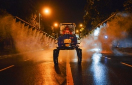 This photo taken on March 2, 2020 shows a worker spraying disinfectant on a road in Yunmeng county, Xiaogan city, in China's central Hubei province. - The world has entered uncharted territory in its battle against the deadly coronavirus, the UN health agency warned, as new infections dropped dramatically in China on March 3 but surged abroad with the US death toll rising to six. (Photo by STR / AFP) /