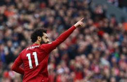 Liverpool's Egyptian midfielder Mohamed Salah celebrates with teammates after he scoring his team's first goal during the English Premier League football match between Liverpool and Bournemouth at Anfield in Liverpool, north west England on March 7, 2020. (Photo by GEOFF CADDICK / AFP) / RESTRICTED TO EDITORIAL USE. No use with unauthorized audio, video, data, fixture lists, club/league logos or 'live' services. Online in-match use limited to 120 images. An additional 40 images may be used in extra time. No video emulation. Social media in-match use limited to 120 images. An additional 40 images may be used in extra time. No use in betting publications, games or single club/league/player publications. /