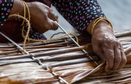 A woman engaging in the process of 'Fangi Vinun' or thatch weaving. PHOTO: UTHEMA