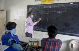 A teacher (C) wearing a facemask teaches as students attend the class at a governement-run high school in Secunderabad, the twin city of Hyderabad, on March 4, 2020, as part of health measures taken against the COVID-19 coronavirus outbreak. PHOTO: NOAH SEELAM / AFP