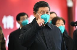 This photo released on March 10, 2020 by China's Xinhua News Agency shows Chinese President Xi Jinping wearing a mask as he GESTURES to a coronavirus patient and medical staff via a video link at the Huoshenshan hospital in Wuhan, in China's central Hubei province on March 10, 2020. PHOTO: AFP