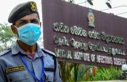 A security personnel wearing a facemask stands guard at the entrance of Sri Lanka's National Institute of Infectious Diseases (IDH) near Colombo on March 12, 2020. (Photo by ISHARA S. KODIKARA / AFP)