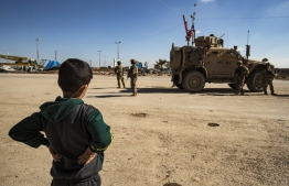 A boy stands near a US military armoured vehicle in the town of Tal Tamr along the M4 highway in the northeastern Syrian Hasakeh province, near the border with Turkey, on March 3, 2020. (Photo by Delil SOULEIMAN / AFP)
