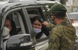 A soldier checks the temperature of a car passenger at a checkpoint before entering Manila on March 16, 2020, as part of measures to reduce the spread of the COVID-19 pandemic. - The virus has upended society around the planet, with governments imposing restrictions rarely seen outside war-time, including the closing of borders, home quarantine orders and the scrapping of public events. (Photo by Maria TAN / AFP)