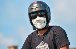 Malé, March 19, 2020: A man in helmet wearing a helmet and face mask. Many residents in Malé city are seen wearing face masks to prevent the spread of COVID-19. PHOTO: AHMED AWSHAN ILYAS/MIHAARU