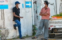 Malé, March 19, 2020: Two men wearing face masks pictured engage in a conversation on the side of a street in Malé city. PHOTO: AHMED AWSHAN ILYAS/MIHAARU