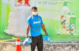 Malé, March 19, 2020: A man walking home with bags of groceries seen wearing a face. Residents in Malé are increasingly seen wearing the face mask amidst the COVID-19 outbreak. PHOTO: AHMED AWSHAN ILYAS/MIHAARU