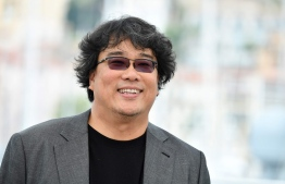 "South Korean director Bong Joon-Ho smiles during a photocall for the film ""Parasite (Gisaengchung)"" at the 72nd edition of the Cannes Film Festival in Cannes, southern France, on May 22, 2019. (Photo by Alberto PIZZOLI / AFP)"