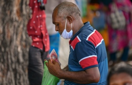 Malé, March 19, 2020: A man pictured paying for his goods wears a mask as a preventive measure against the COVID-19. PHOTO: AHMED AWSHAN ILYAS/MIHAARU