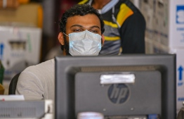 Malé, March 19, 2020: A man pictured sitting at his desk at the local market wears a face mask as he works. Health professionals however advised against the use of surgical masks, unless an individual showed symptoms for COVID-19. PHOTO: AHMED AWSHAN ILYAS/MIHAARU