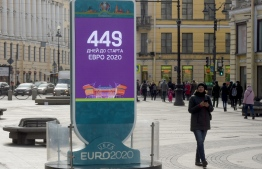 A woman walks past the Euro 2020 countdown clock - displaying 449 days left before the event - in downtown Saint Petersburg on March 19, 2020. - The European Championship, due to be played in June and July this year, has been postponed until 2021 because of the coronavirus pandemic, European football's governing body UEFA said on March 17, 2020. UEFA announced that the new proposed dates for the tournament were June 11 to July 11 next year, as Euro 2020 becomes Euro 2021. (Photo by OLGA MALTSEVA / AFP)