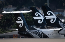 Air New Zealand airplanes wait for passengers outside the international terminal as a plane taxis (L) at Wellington International airport on February 20, 2020. - The New Zealand government announced a bail out package to help the national carrier Air New Zealand survive the Corvid 19 virus down turn. PHOTO: MARTY MELVILLE / AFP