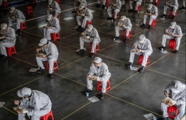 This photo taken on March 23, 2020 shows employees eating during lunch break at an auto plant of Dongfeng Honda in Wuhan in China's central Hubei province. - People in central China, where the COVID-19 coronavirus was first detected, are now allowed to go back to work and public transport has restarted, as some normality slowly returns after a two-month lockdown. (Photo by STR / AFP) /