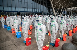 Staff members line up at attention as they prepare to spray disinfectant at Wuhan Railway Station in Wuhan in China's central Hubei province on March 24, 2020. - China announced on March 24 that a lockdown would be lifted on more than 50 million people in central Hubei province where the COVID-19 coronavirus first emerged late last year. (Photo by STR / AFP) /
