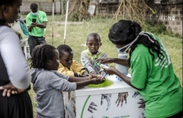 A worker instructs several kids on how to wash properly their hands at the entrance of the Mbagathi Hospital in Nairobi, Kenya on March 18, 2020. - The Government of Kenya confirmed new positive cases of COVID-19 coronavirus on March 18, 2020, bringing the total official number of cases in the East African country to 7.  African countries have been among the last to be hit by the global COVID-19 coronavirus epidemic but as cases rise, many nations are now taking strict measures to block the deadly illness. (Photo by LUIS TATO / AFP)