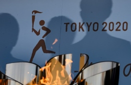 The logo for the Tokyo 2020 torch relay is pictured as the Olympic flame goes on display at the Aquamarine Fukushima aquarium in Iwaki in Fukushima prefecture on March 25, 2020, the day after the historic decision to postpone the 2020 Tokyo Olympic Games. (Photo by Philip FONG / AFP)