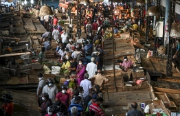 People wearing facemasks buy supplies at a crowded vegetable market at Piliyandala on the outskirts of Sri Lanka's capital city Colombo on March 24, 2020, as the authorities briefly lifted a curfew to allow residents to stock up on essentials amid concerns over the spread of the COVID-19 coronavirus. PHOTO: LAKRUWAN WANNIARACHCHI / AFP