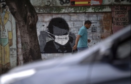 A man walks past a graffiti of Brazilian President Jair Bolsonaro wearing a face mask in downtown Rio de Janeiro, Brazil, on March 24, 2020 during the coronavirus COVID-19 pandemic. - The Rio de Janeiro state government is requesting people not to go to the beach or any other public areas as a measure to contain the coronavirus pandemic. (Photo by Mauro PIMENTEL / AFP)