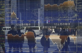 Pedestrians reflected in a window stand in front of a quotation board displaying the numbers on the Tokyo Stock Exchange in Tokyo on March 26, 2020. - Tokyo's key Nikkei index opened down more than three percent on March 26 on profit-taking after surging in recent sessions, although US stimulus plans offset worries over the COVID-19 coronavirus pandemic. (Photo by Kazuhiro NOGI / AFP)