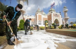 Volunteers disinfects the grounds of Pattani Central Mosque as a preventive measure against the COVID-19 coronavirus in Thailand's southern province of Pattani on March 23, 2020. - Health authorities reported several local Thai pilgrims from Pattani who attended an international Islamic gathering in Malaysia in early March tested positive of coronavirus. PHOTO: TUWAEDANIYA  MERINGING / AFP