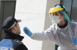 A handout picture released by the Madrid City Hall shows a health worker handling a swab to test a municipal police officer for the COVID-19 coronavirus in Madrid on March 25, 2020. - Spain's coronavirus death toll overtook that of China, rising to 3,434 after another 738 people died as Madrid announced a multi-million-euro deal with Beijing for critical supplies. (Photo by Rafa ALBARRAN / Madrid City Hall / AFP) /
