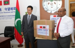 Ambassador Zhang handing over the donations to Minister Shahid, who accept on behalf of Maldivians. PHOTO: FOREIGN MINISTRY