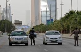 A picture taken on March 26, 2020, shows Saudi policemen manning a checkpoint on King Fahd road in the capital Riyadh. (Photo by FAYEZ NURELDINE / AFP)