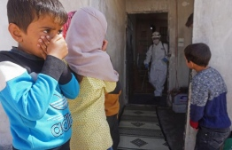 Children observe an individual wearing personal protective equipment during the COVID-19 pandemic. PHOTO: UNICEF