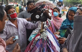 People in Bangladesh, shopping in masks. A total of 41 Maldivians are currently residing in Bangladesh. PHOTO: AFP