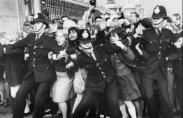 """(FILES) In this file photo taken on October 26, 1965 fans of the British group The Beatles are held back by police at the fence of Buckingham Palace, central London, during a public appearance by the group when they were received by Britain's Queen Elizabeth II. - When the members of the Beatles went their separate ways in the early 1970s, few predicted that half a century later the iconic band would still dominate pop music culture. But, with Friday marking the 50th anniversary of their unofficial break-up, the so-called """"Fab Four"""" appear as popular and omnipresent as ever. (Photo by - / AFP)"""