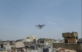 A drone is used to spray disinfectant over residential areas during a government-imposed nationwide lockdown as a preventive measure against the COVID-19 coronavirus, in Ahmedabad on April 9, 2020. (Photo by SAM PANTHAKY / AFP)