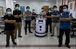 Engineering professors pose with the version two prototype of the IIUM Medibot medical robot, being developed for health workers to treat patients without risking infection from the COVID-19 coronavirus, at the International Islamic University Malaysia in Gombak, on the outskirts of Kuala Lumpur, on April 13, 2020. (Photo by Mohd RASFAN / AFP)