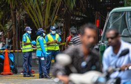 Police near an area cordoned off in capital city Male', following the first local transmission of COVID-19. PHOTO: AHMED ASHWAN ILYAS / MIHAARU
