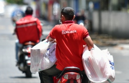 Employees of local delivery service 'Red Box', course through the streets of Male' armed with bags upon bags, each more strained than the next by the weight of all the essential goods ordered by residents in need. PHOTO: AHMED AWSHAN ILYAS / MIHAARU
